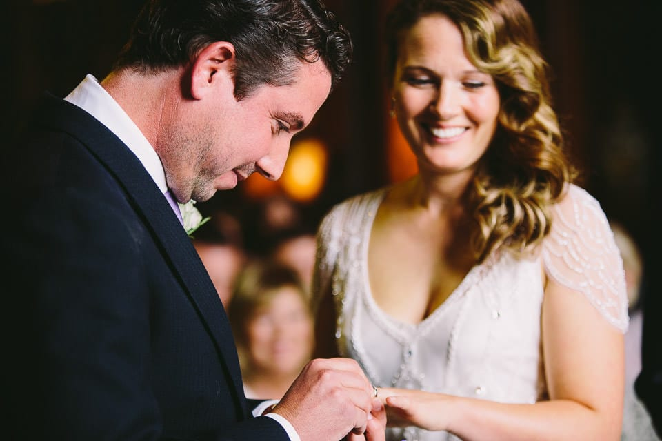 Groom placing wedding ring on brides finger