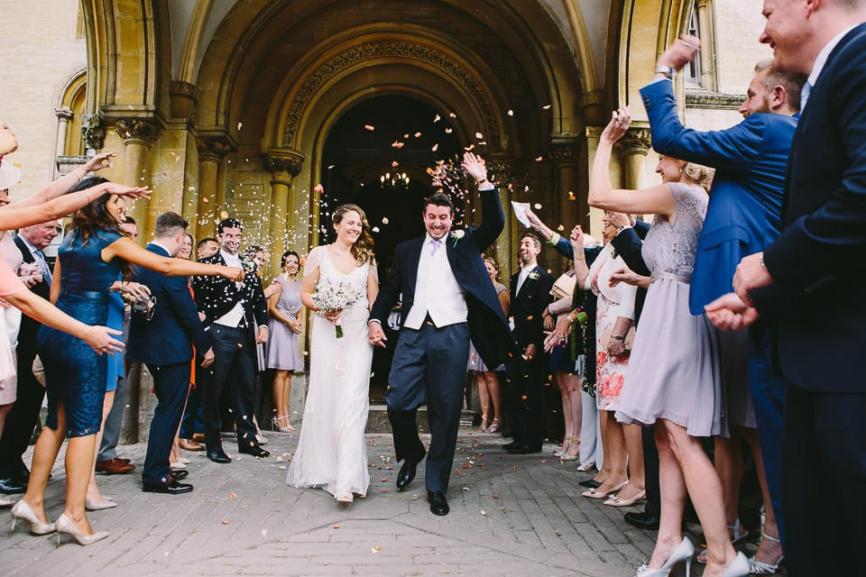 Confetti being thrown over bride and groom outside