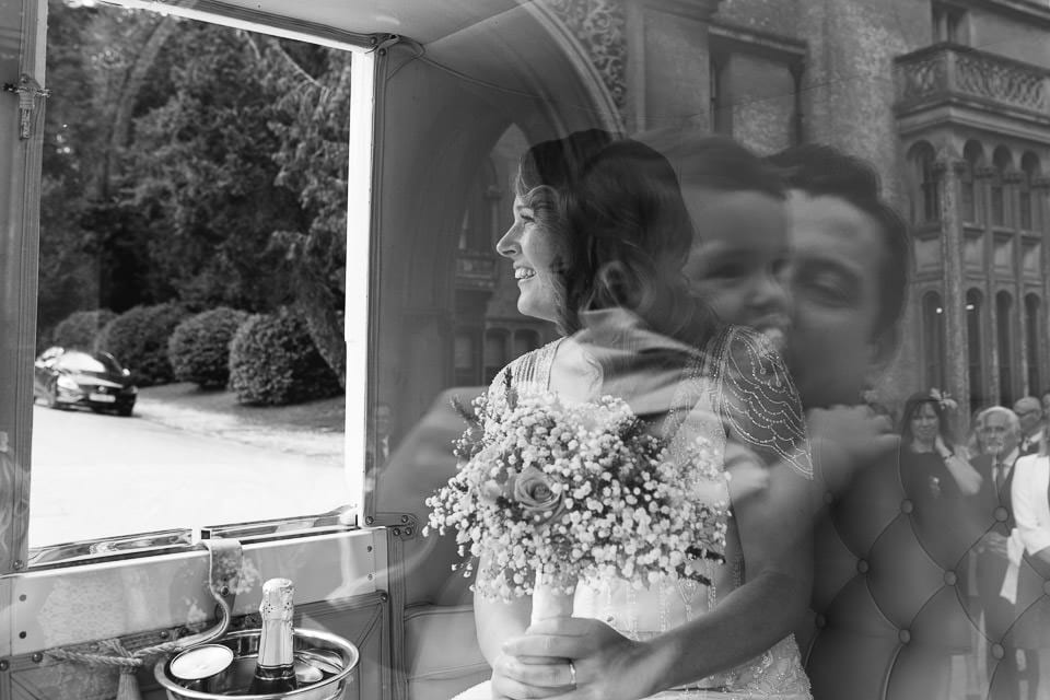 Black and white image of bride in carriage with groom and baby reflected in window