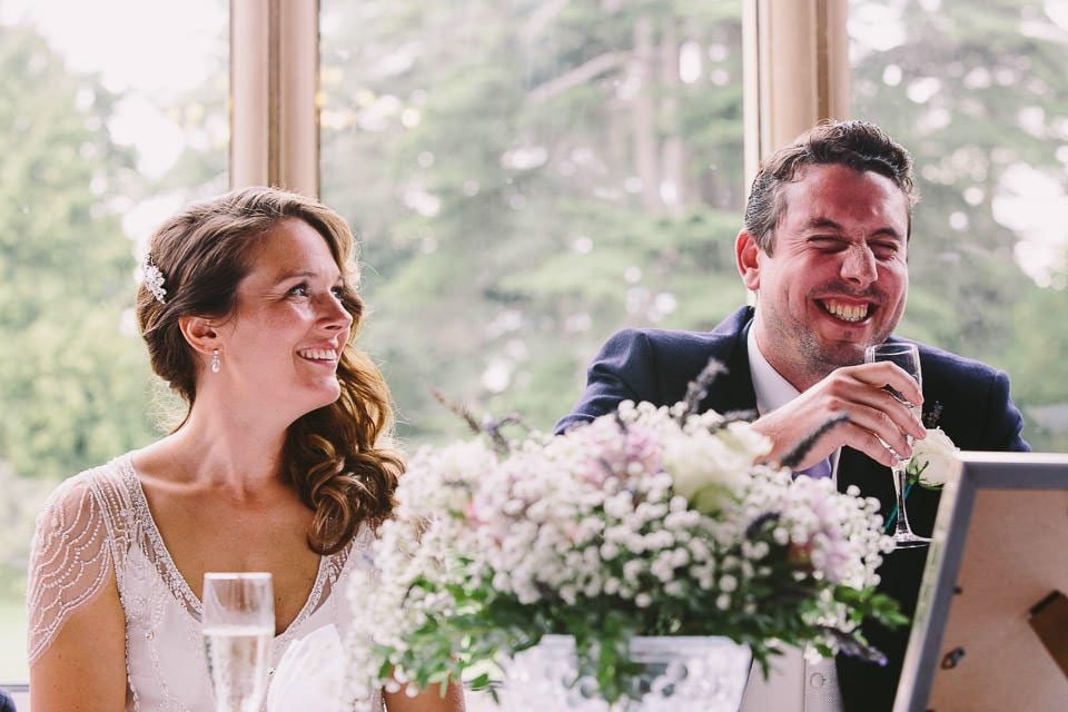 Bride and groom laughing during speech