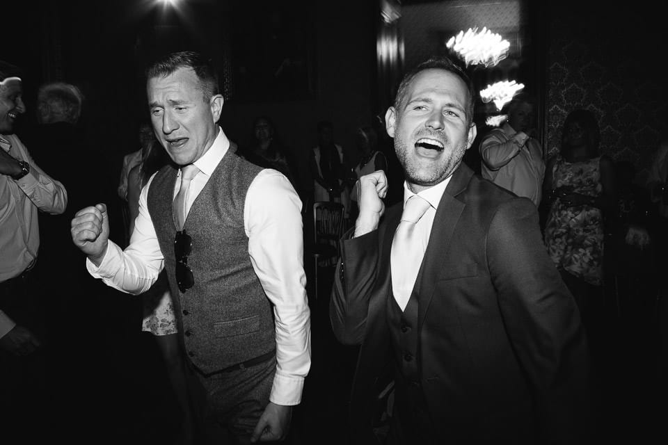 Black and white image of male guests dancing