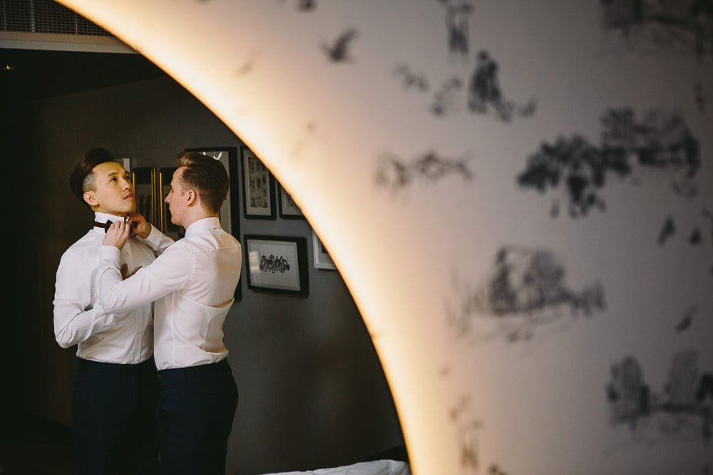Reflection in mirror of one groom tying the other grooms bow tie at The Hoxton London