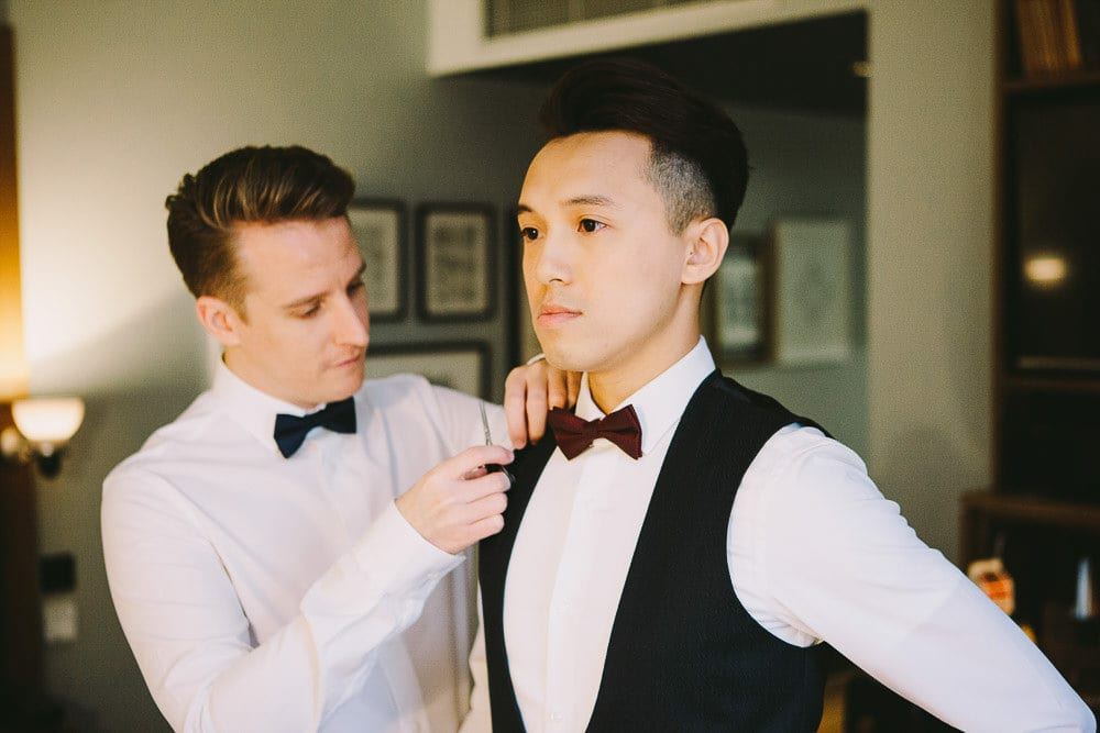 Groom adjusting his partners waistcoat at The Hoxton London
