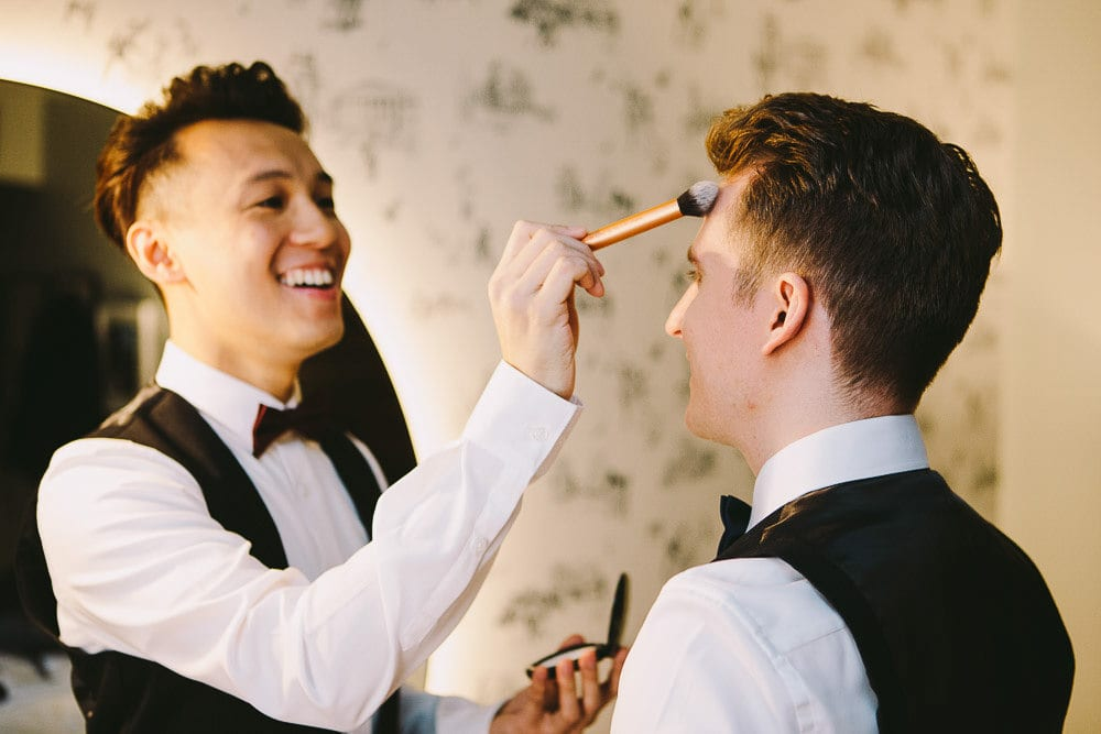Groom applying a bit of make up on his partner at The Hoxton London