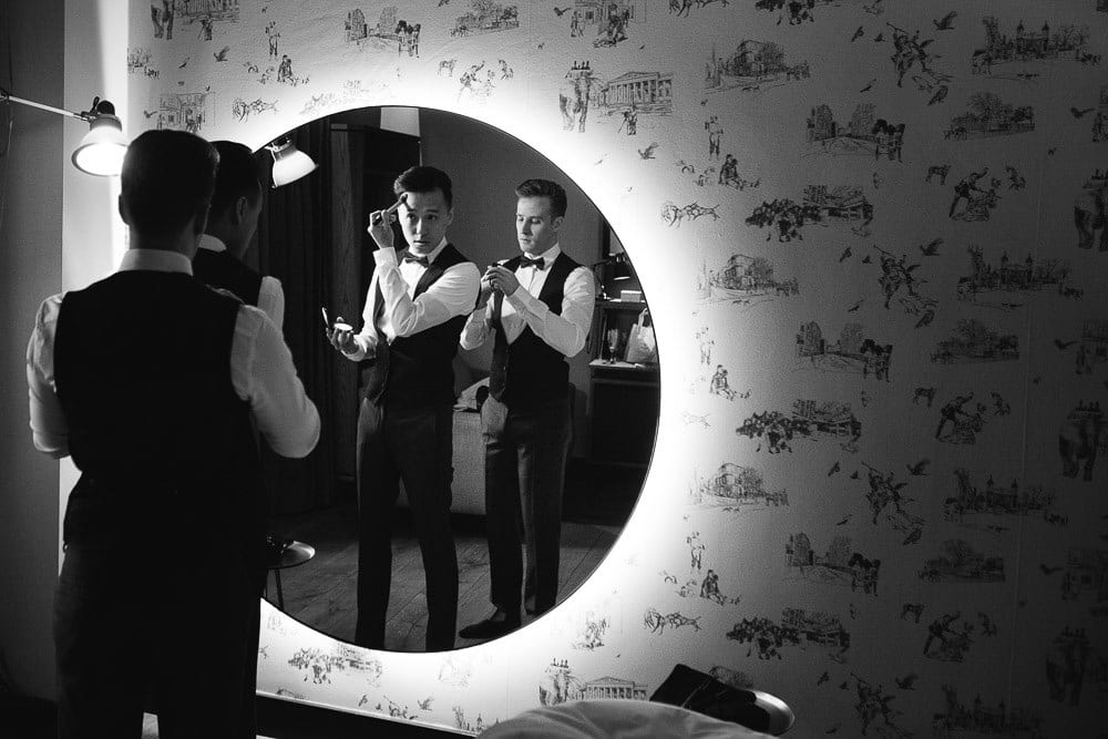 Both grooms looking in the full length mirror at The Hoxton London