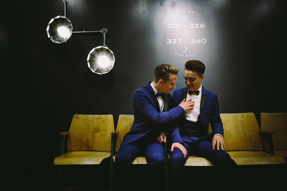 Both grooms sitting while waiting for the lift in The Hoxton London