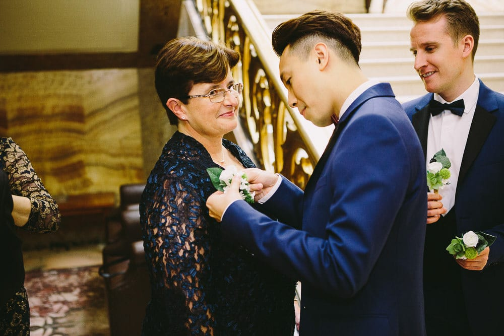 Groom helping mum to put on her buttonhole before the wedding