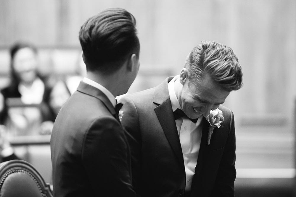 Black and white image of both grooms during ceremony