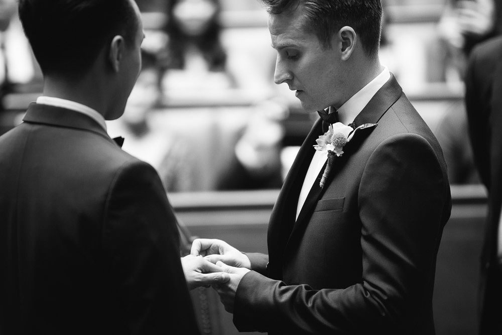 Grooms exchanging rings during the ceremony in Wandsworth Town Hall