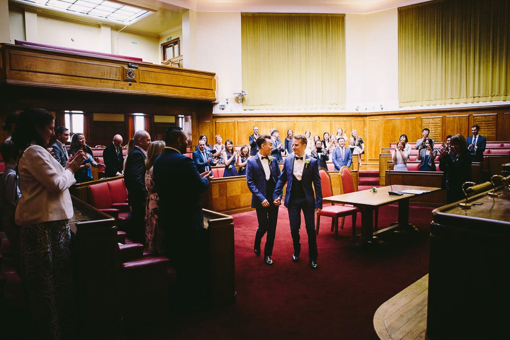 Grooms exiting the Grand Chamber after their wedding at Wandsworth Town Hall