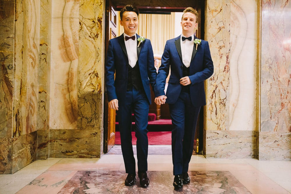 Both grooms walking out of the Grand Chamber