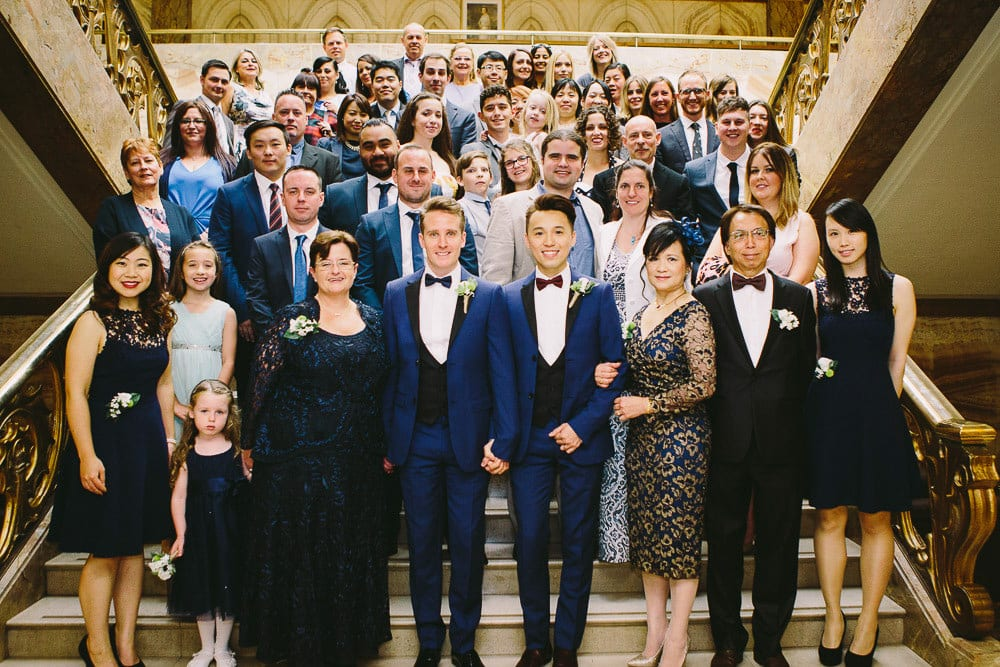 Group photo of wedding party on the marble staircase at Wandsworth Town Hall