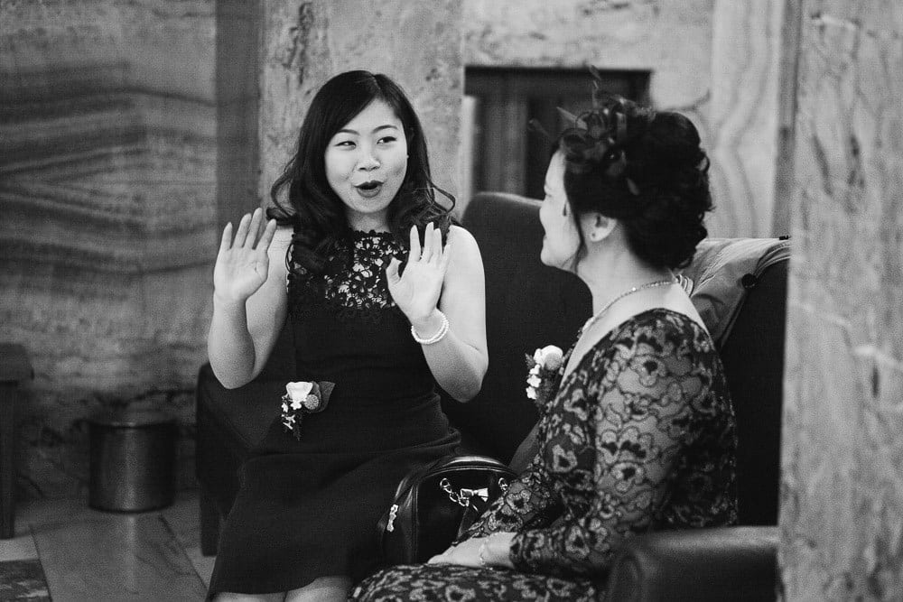 Mother of the groom and bridesmaid sharing a joke in Wandsworth Town Hall
