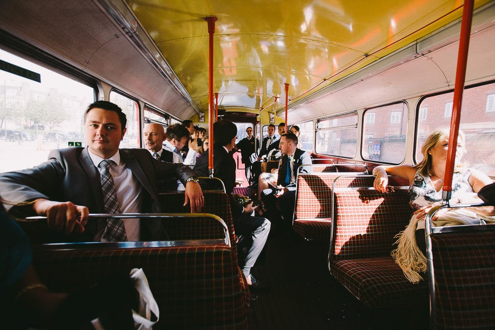 Grooms and their guests travelling on vintage bus back to The Hoxton London