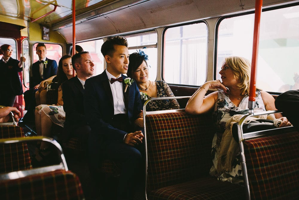 Groom sitting next to his mother on the vintage bus back to The Hoxton London