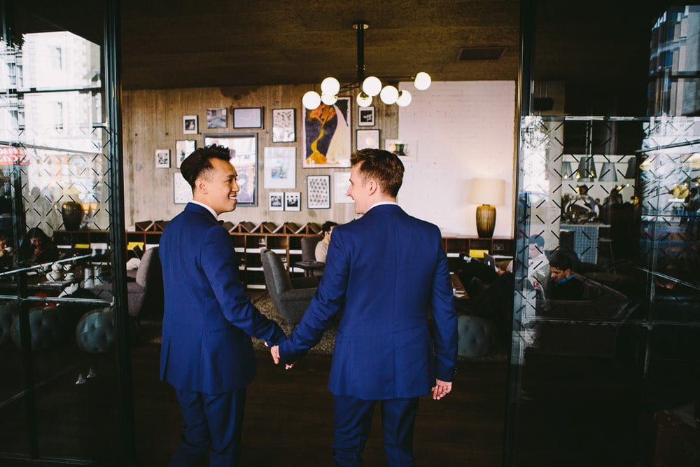 Grooms walking through the lobby of The Hoxton London