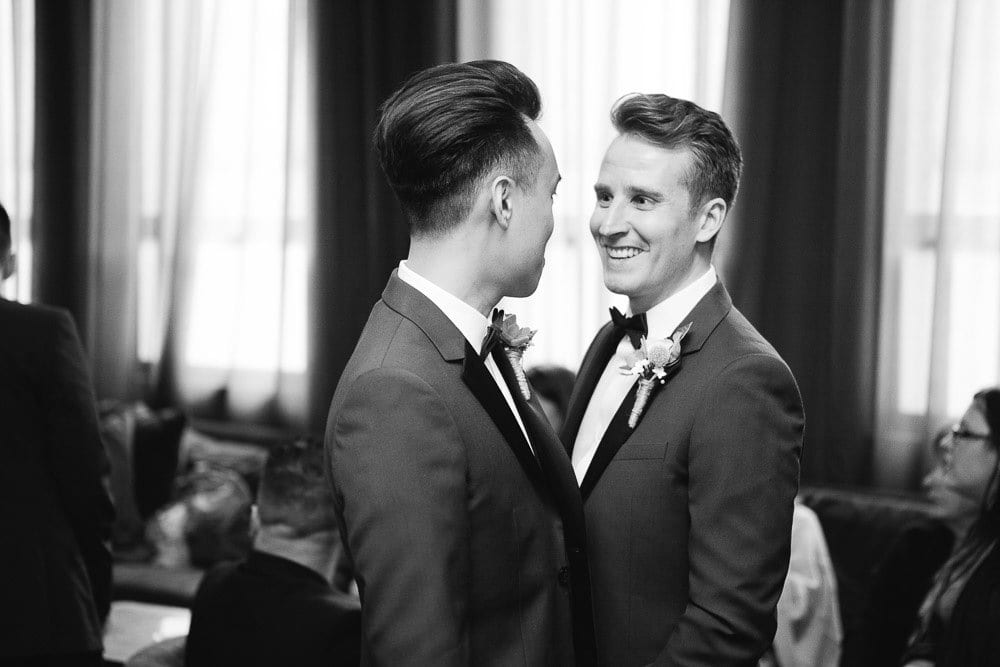 Grooms laughing with each other at their wedding reception in The Hoxton London