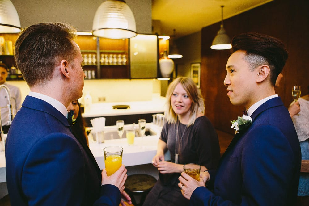 Grooms chatting to one of their guests at the bar