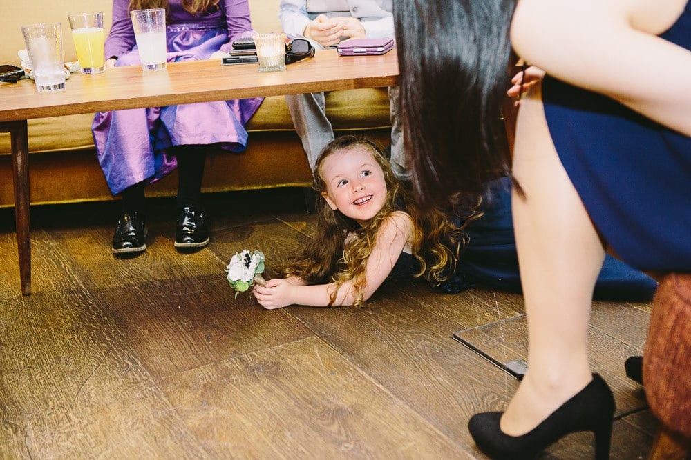 Flower girl under the table at the reception in The Hoxton London
