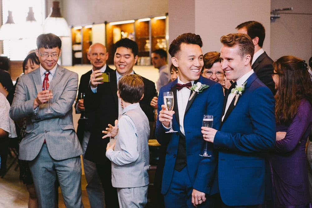 Grooms enjoying the speech at their reception at The Hoxton London