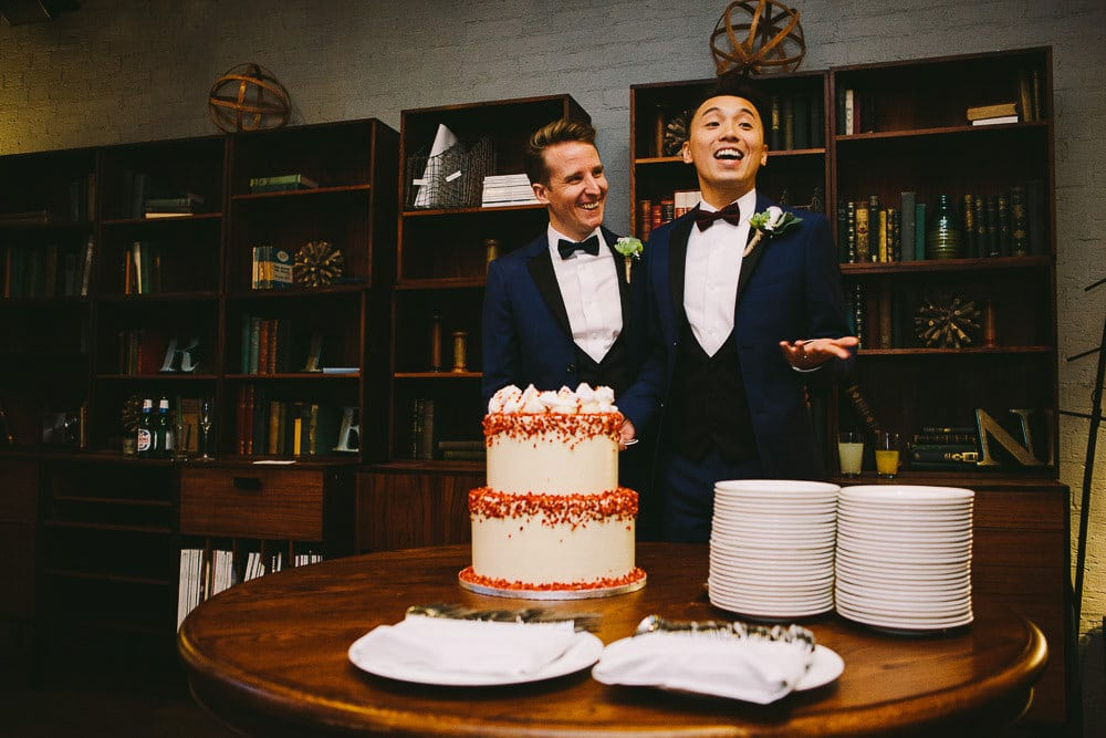 Grooms getting ready to cut their cake in The Hoxton London