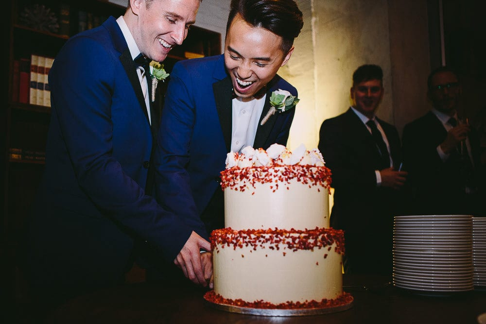 Both grooms cutting their wedding cake in The Hoxton London