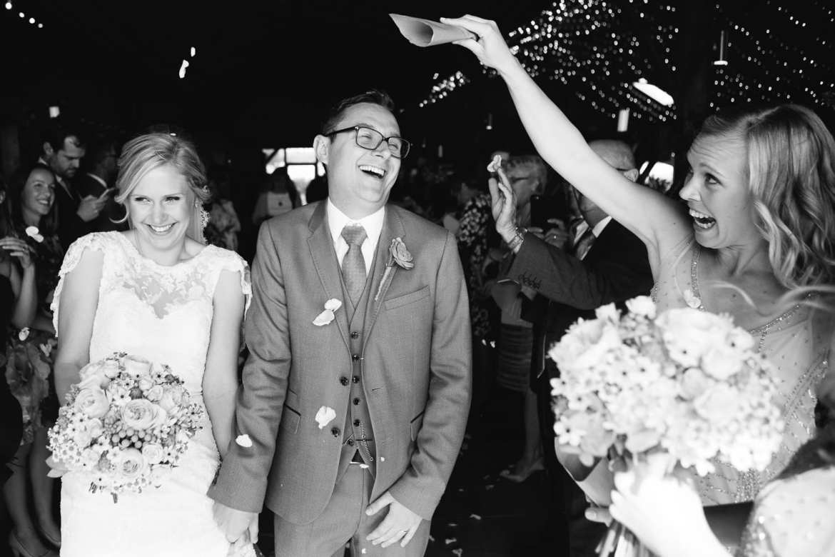 Black and white image of couple and bridesmaid throwing confetti