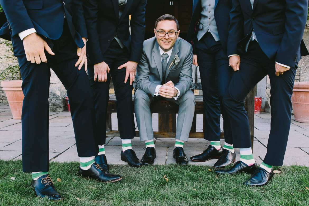 Groom seated with his groomsmen showing off their stripey socks