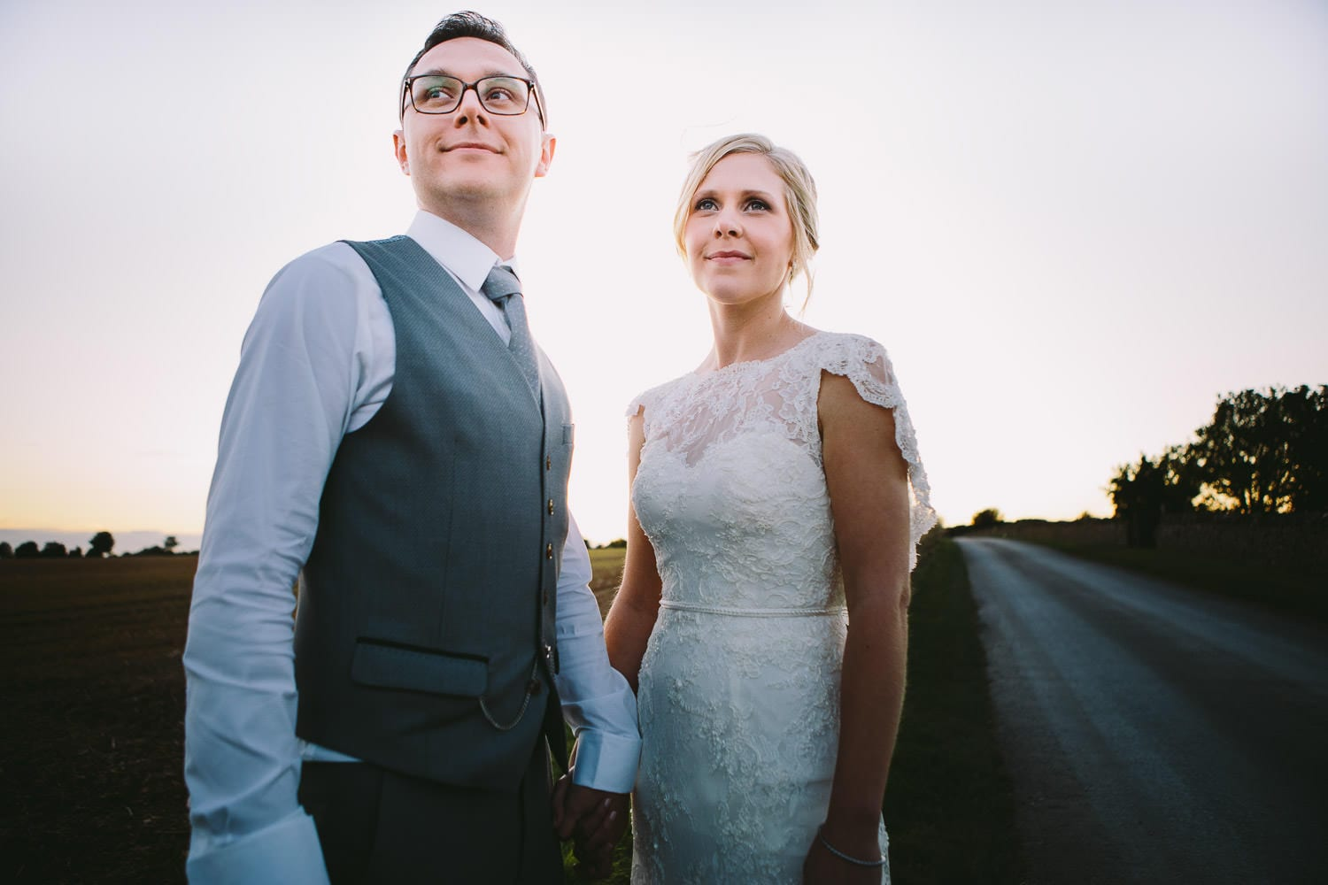 The bride and groom standing in the Cotswolds countryside