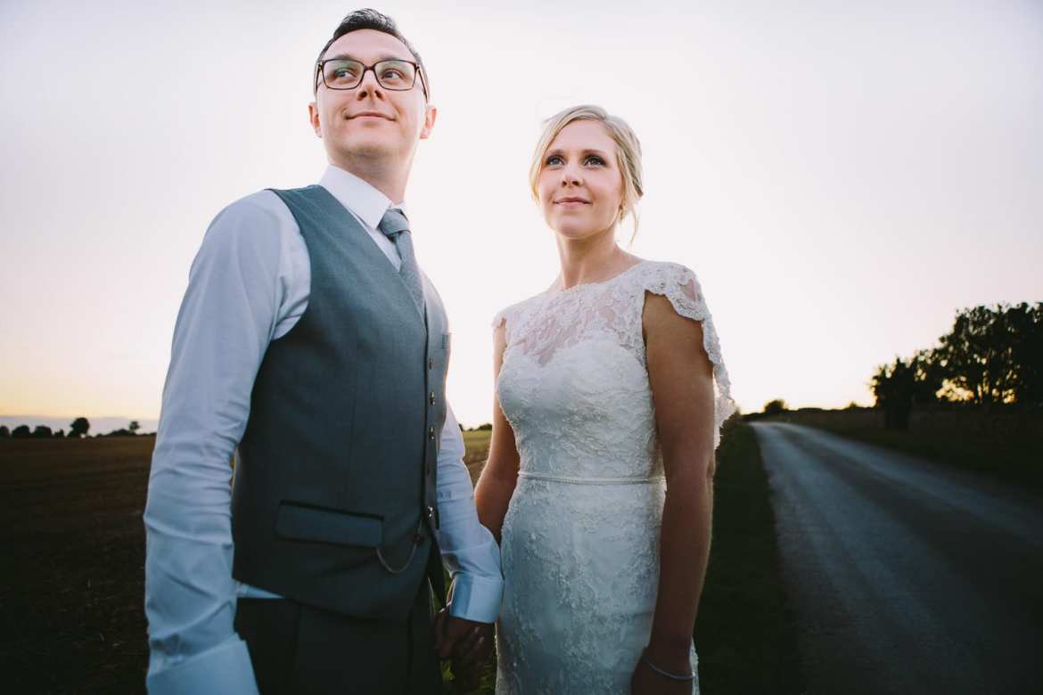 Bride and groom standing next to the driveway at sunset