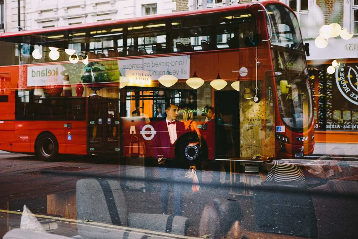 Image of groom through hotel lobby window with reflection of London bus going past