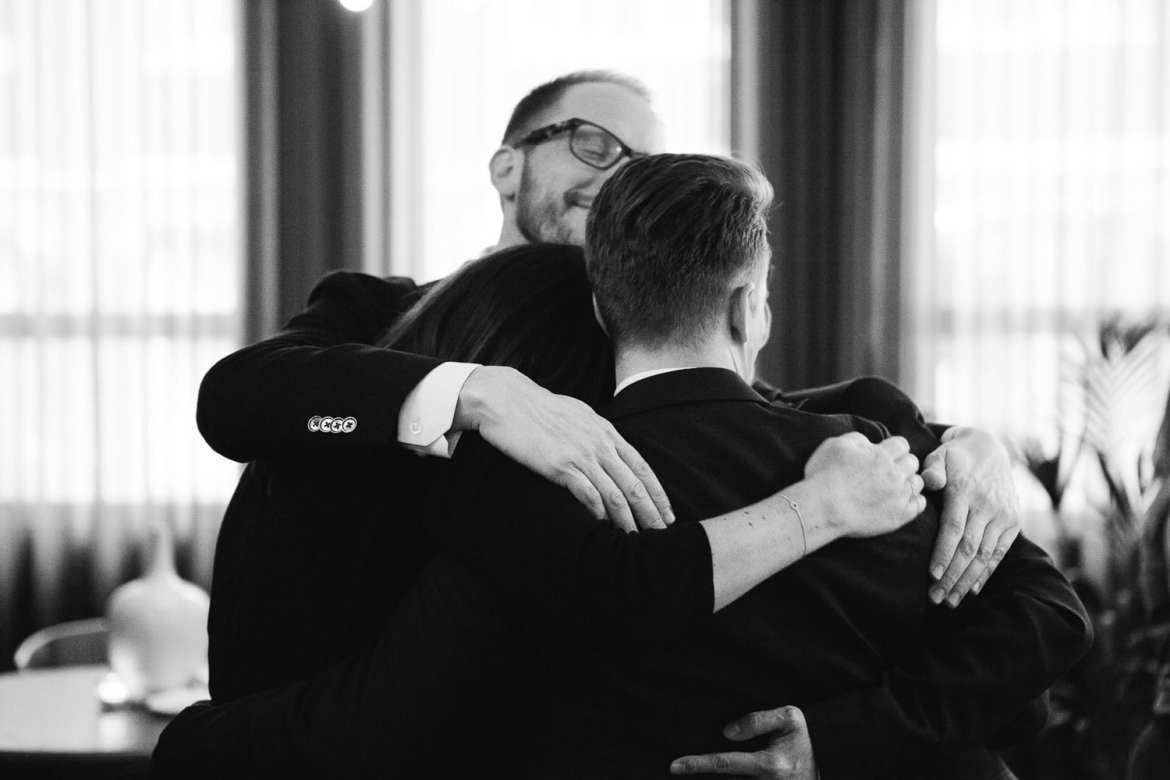 Black and white image of a group hug with friends