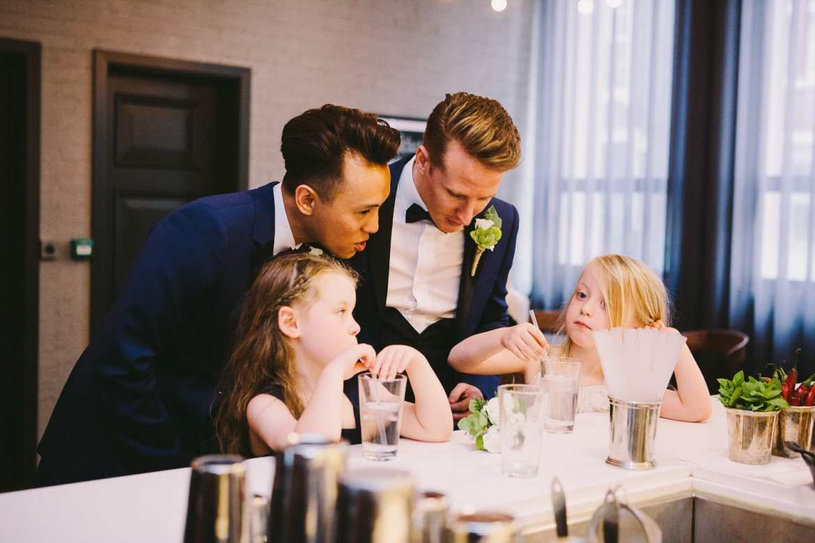 Couple chatting with their flower girls at the bar