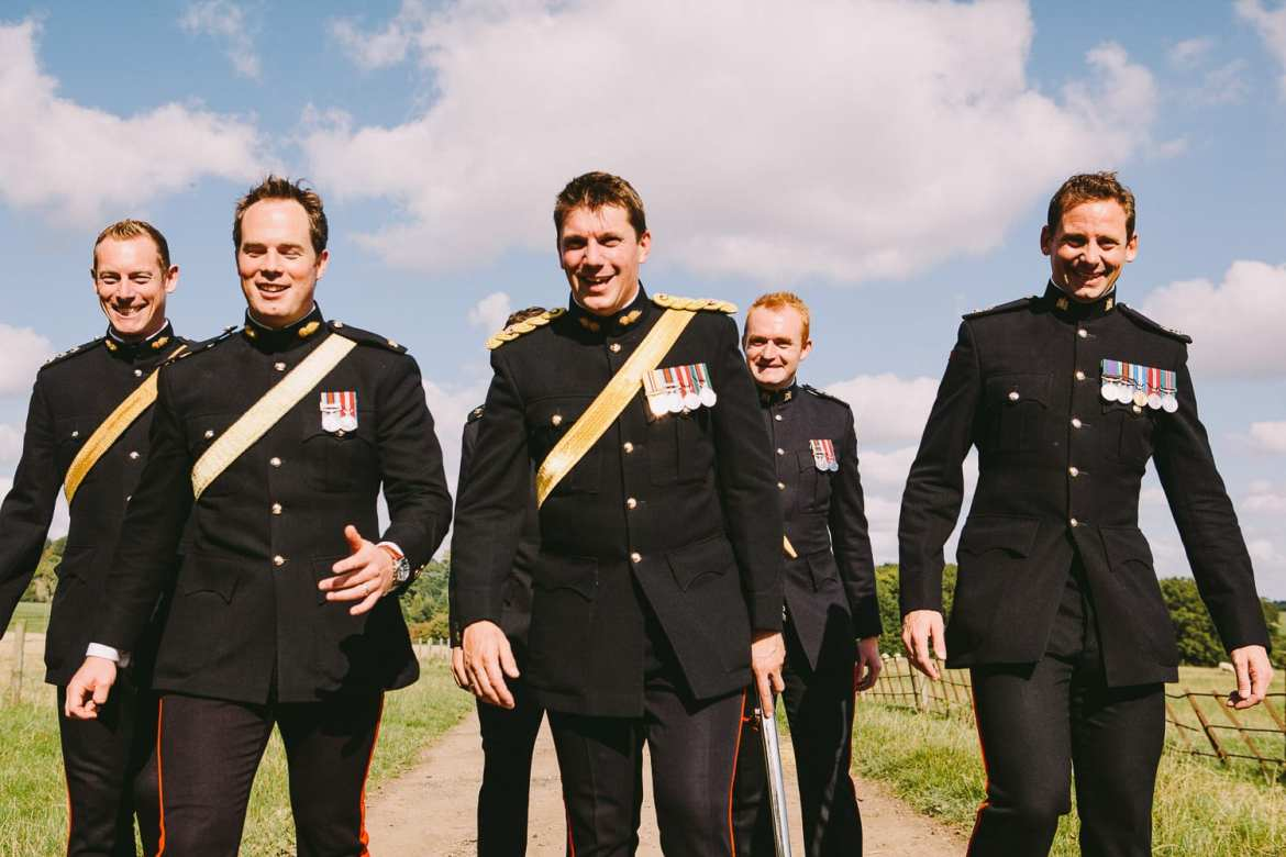 Groom and his military honour guard walking down lane