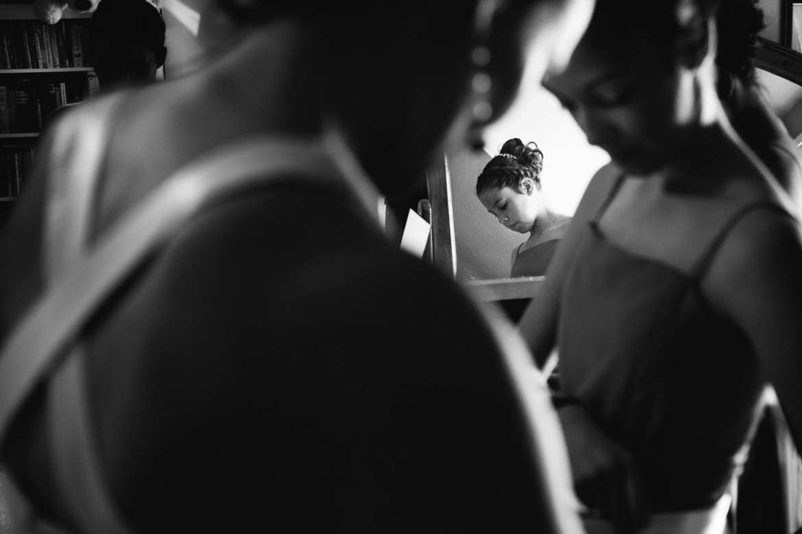 Black and white image of bridesmaid reflected in mirror