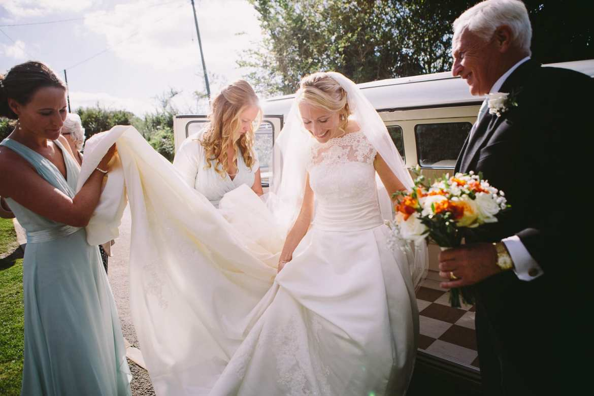 Bride getting out of VW Camper with her father
