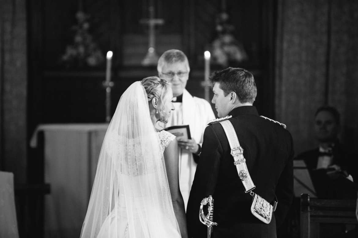 Black and white image of couple at altar