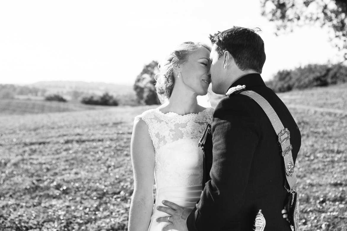 Black and white image of couple in countryside on way to reception