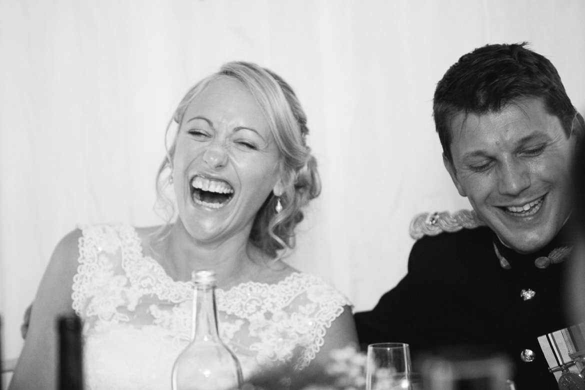 Black and white shot of couple laughing at best man speech