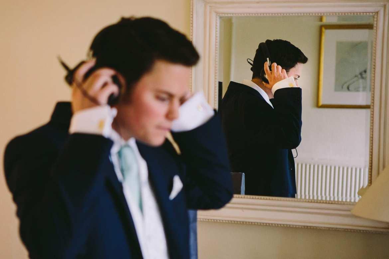 Groom wearing headphones while getting ready