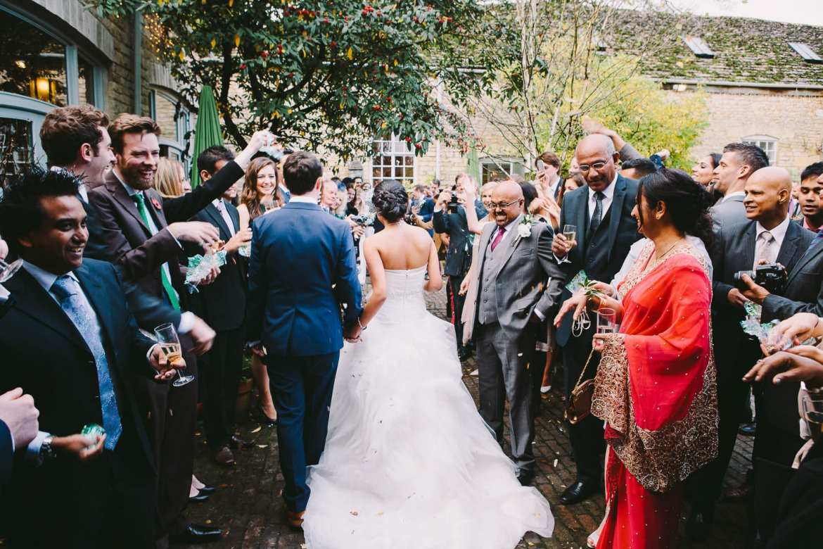 The bride and groom walking while guests throw confetti