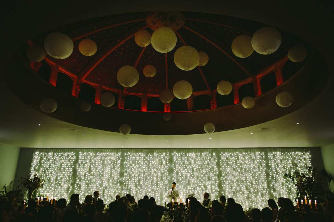 The grooms speech showing the room decoration with all the guests in silhoueete