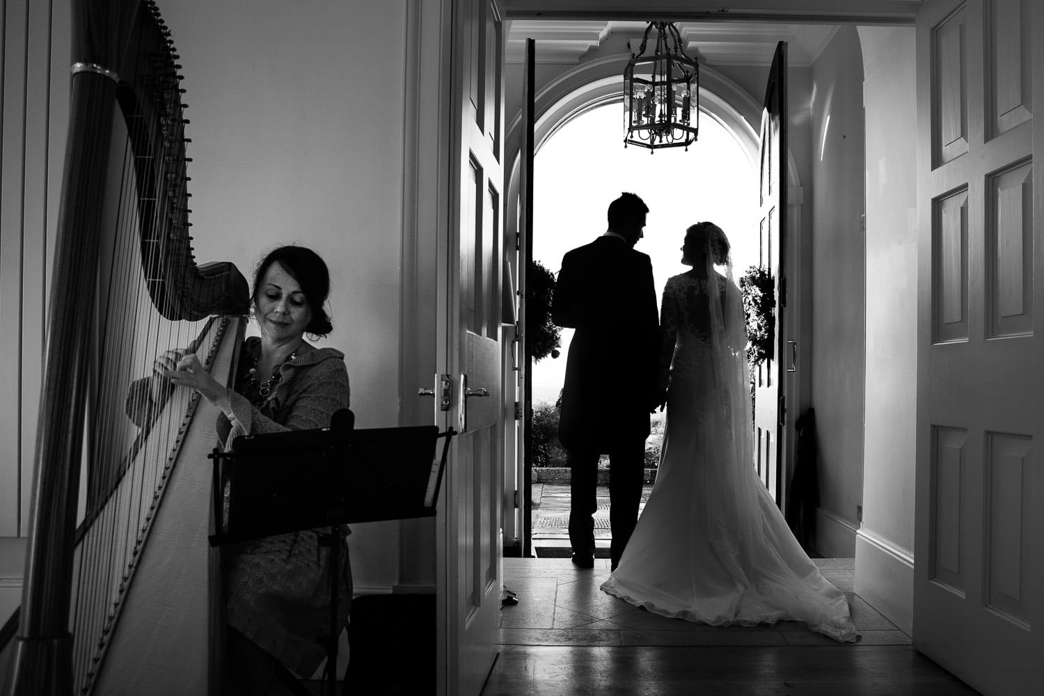 The bride and groom silhoueeted in the doorwat while the harpist plays