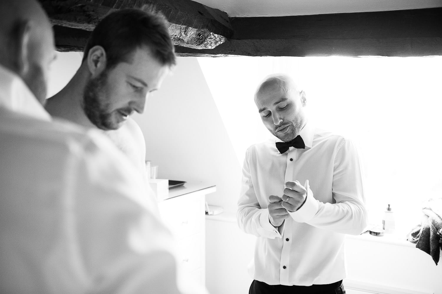 A best man doing his cufflinks up