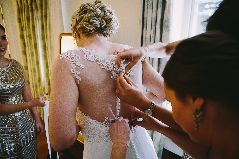 the bridesmaids button up the brides dress