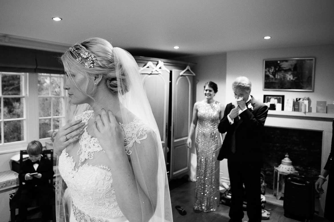 the father of the bride wipes tears from his eyes