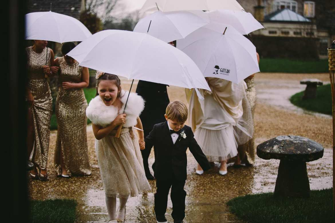 the bridal party under umbrellas in the rain