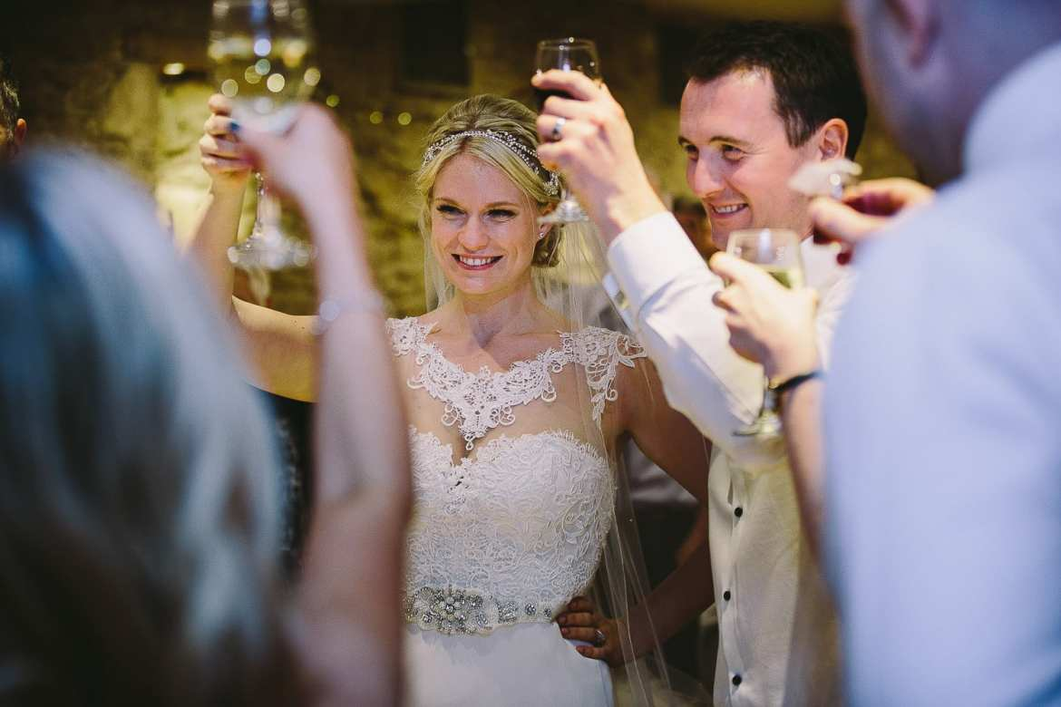 Bride and groom and guests giving a toast during speeches