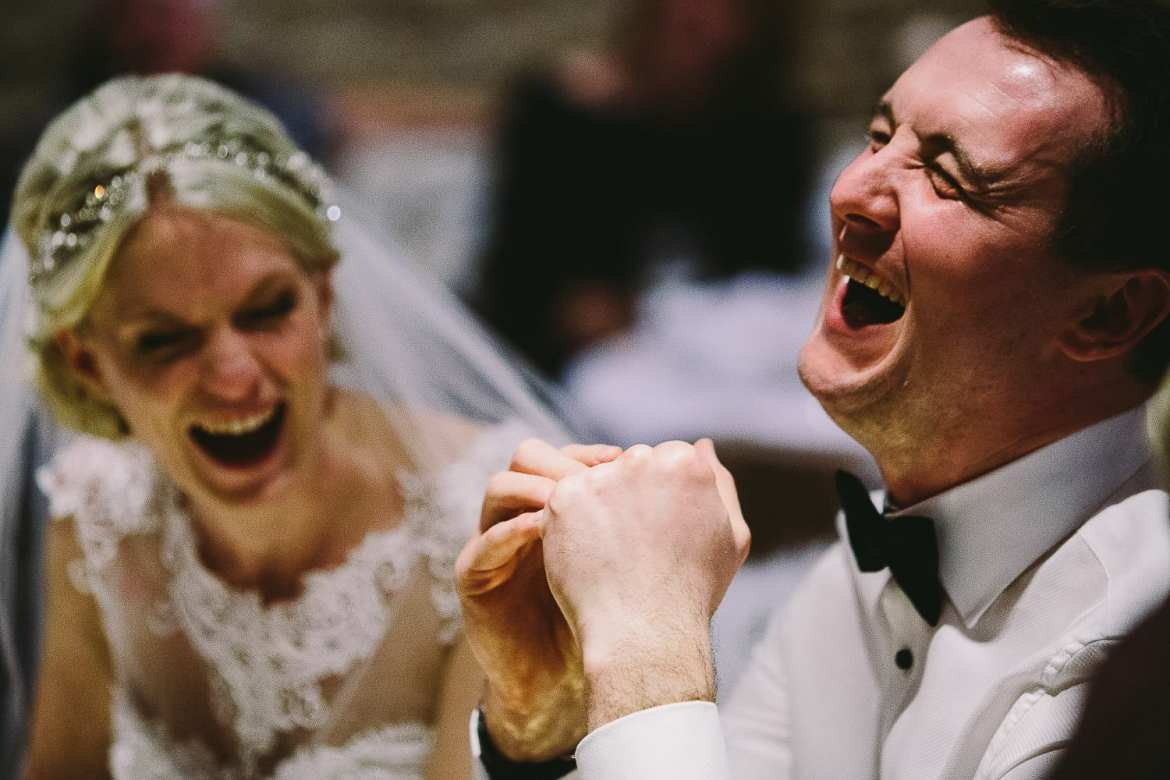 Bride and groom laughing at best mens speech