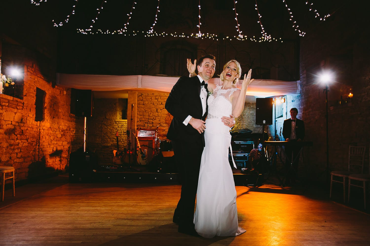 Bride and groom beckoning guests onto the dance floor